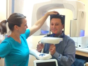 Dental assistant Kristy Loy positions Dr. Gio Iuculano, DDS for a CBCT scan