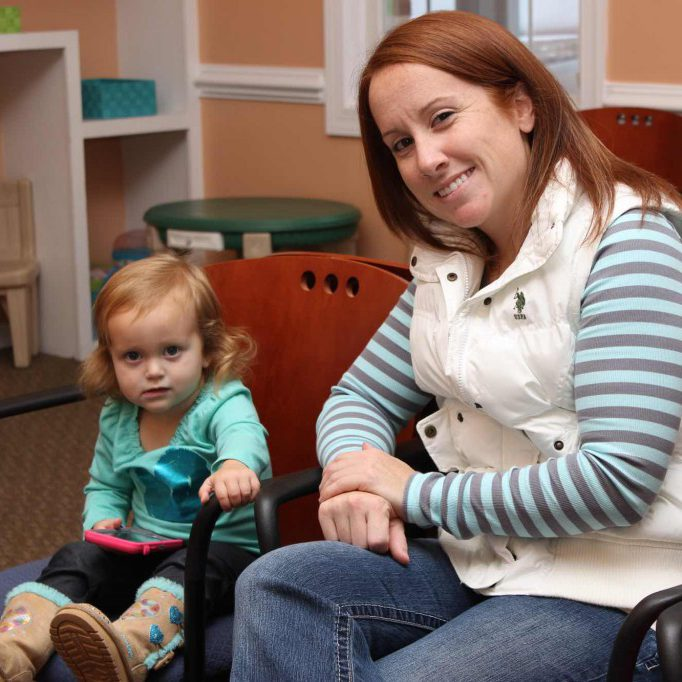 A very young patient and her mother in Winchester Dental's waiting area