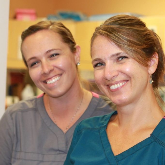 Closeup of two smiling dental assistants, Staci Kubovcik and Kristy Loy