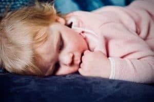 A young child sucks her fingers as she falls asleep. Photo credit: Jelleke Vanooteghem on Unsplash