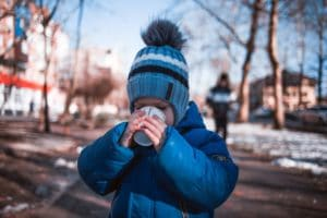 Outdoor winter scene with a young child drinking from a cup. Teach your child to drink from a regular cup by the age of 18 months or so. Photo credit: Vladislav Nikonov on Unsplash