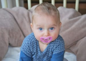 Young child in blue outfit with pink pacifier in mouth.