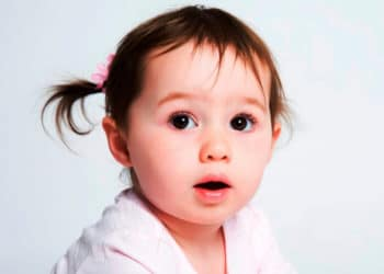 Closeup of toddler girl with dark eyes and a pigtail. A dentist might be the first to spot signs of celiac disease in your child.