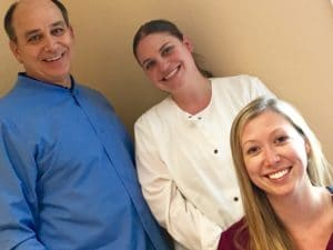 Diagonal photo of Dr. Frank Mitchell, DDS and assistants Jennifer Bretza, and Samantha Ruble