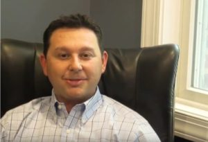 Dr. Gio Iuculano, DDS seated in leather chair
