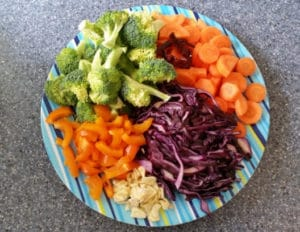 Photo of a plate of colorful healthy foods, including raw broccoli, carrots, red cabbage, sweet pepper, and cauliflower