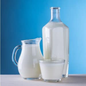 Photo of a pitcher of milk, bottle of milk, and a glass of milk against a blue background