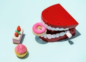 Mechanical teeth with frosted donut, petit fours, and cupcake. Taking a few minutes to floss daily is vital to oral and overall health.