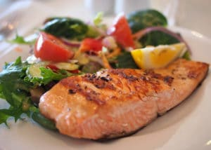 Dinner plate with colorful food including red tomatoes, green vegetables, and roast salmon