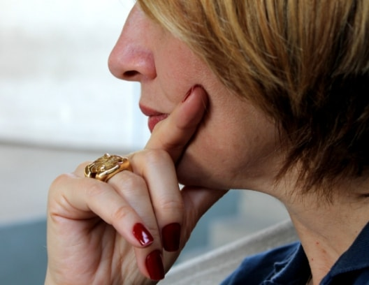 Closeup of a woman squeezing her mouth area. Sensitive teeth may be the reason.