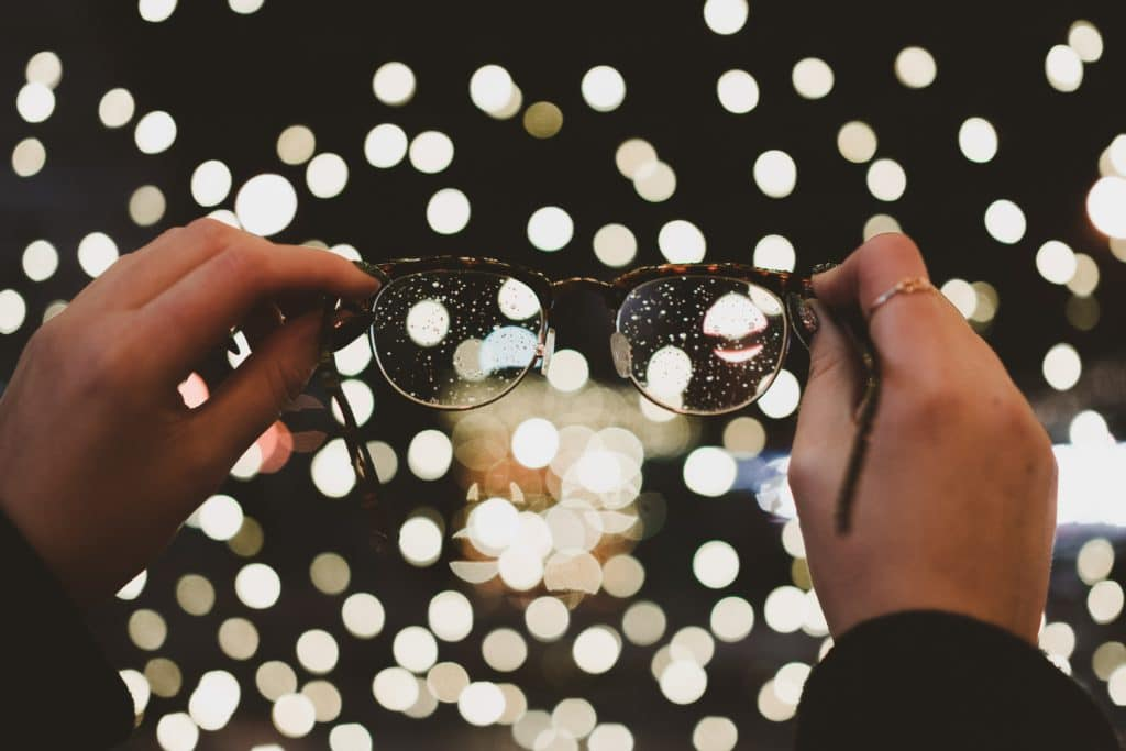 Closeup of hands holding pair of eyeglasses before background of many small lights reflections resembling pearls