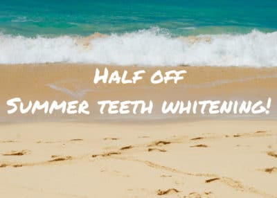 """Ocean waves crashing onto a sandy beach with the words """"Half off summer teeth whitening"""" superimposed on the sand"""