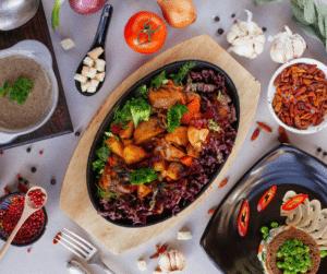 A colorful vegan feast including potato casserole with broccoli and carrot, fresh tomato, tofu, onion, and mushrooms.