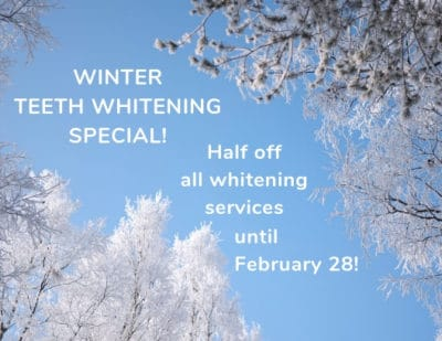 Winter scene: text announcing a winter teeth whitening special on a photo of snow covered trees against a blue sky.